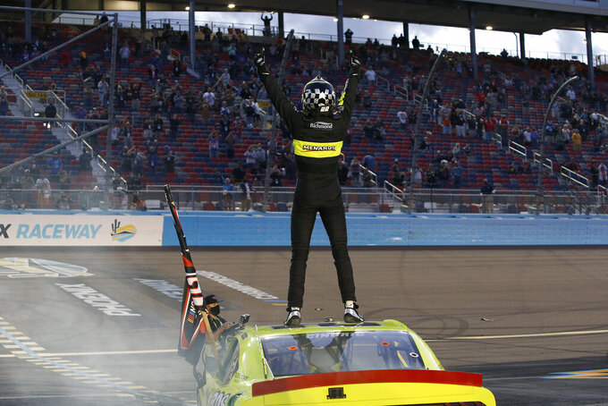 Austin Cindric stands on the roof of his race car to acknowledge the crowd after winning the season championship and a NASCAR Xfinity Series auto race at Phoenix Raceway, Saturday, Nov. 7, 2020, in Avondale, Ariz. (AP Photo/Ralph Freso)