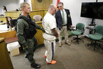 Curtis Watson, center, is escorted out of a preliminary hearing as it is recessed Wednesday, Nov. 20, 2019, in Ripley, Tenn. Watson is charged with murdering Tennessee Department of Correction department administrator Debra Johnson after Watson escaped from the West Tennessee State Penitentiary in August. (AP Photo/Mark Humphrey, Pool)