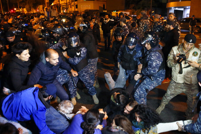 Protesters lie on a road, as they scream and hold each others while riot police try to remove them and open the road, in Beirut, Lebanon, Wednesday, Dec. 4, 2019. Protesters have been holding demonstrations since Oct. 17 demanding an end to widespread corruption and mismanagement by the political class that has ruled the country for three decades. (AP Photo/Bilal Hussein)