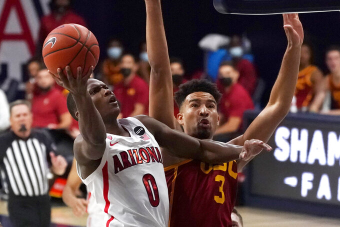 Arizona guard Bennedict Mathurin (0) drives on Southern California forward Isaiah Mobley during the second half of an NCAA college basketball game, Thursday, Jan. 7, 2021, in Tucson, Ariz. (AP Photo/Rick Scuteri)