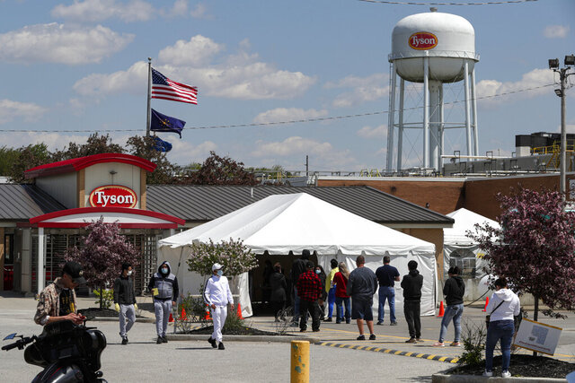 Workers line up to enter the Tyson Foods pork processing plant in Logansport, Ind., Thursday, May 7, 2020. In Cass County, home to the Tyson plant, confirmed coronavirus cases have surpassed 1,500. That's given the county — home to about 38,000 residents — one of the nation's highest per-capita infection rates. (AP Photo/Michael Conroy)