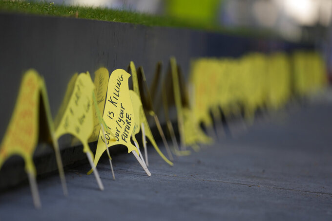 Protesters put yellow canary shaped hand written messages outside the Home Office, during a demonstration against a proposed coking coal mine Cumbria in the north of England, in London, Tuesday, Sept. 7, 2021. The U.K. has opened a public inquiry into plans for the country's first new deep coal mine in three decades amid complaints that permitting the project would send the wrong message as the government seeks to persuade other countries to give up coal. Communities Secretary Robert Jenrick ordered the investigation in March, saying the project may conflict with the government's target for reaching net zero carbon emissions by 2050. (AP Photo/Alastair Grant)
