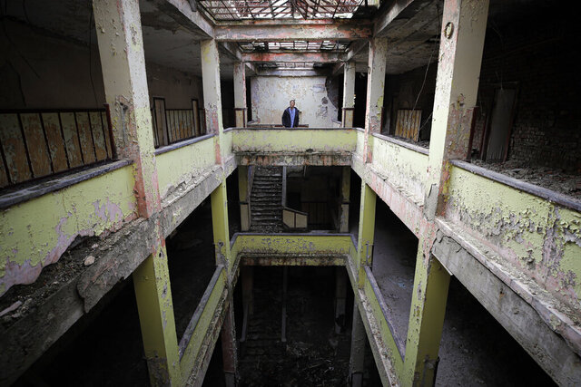 In this photo taken on Monday, Dec. 16, 2019, Florin Catanescu, 41, walks through the ruins of the state orphanage that was his home between 1988 and 1997 in Busteni, Romania. Thirty years after the 1989 death of Romania's communist-era dictator, the country is still grappling with the ugly legacy of its once-horrific orphanages. Now some of those who grew up abused and unloved in those failed institutions are turning their trauma into commitment. Florin Catanescu, who lived in an orphanage until 1997, now runs a transition home helping those leaving state care to have a better chance of leading meaningful lives. (AP Photo/Vadim Ghirda)