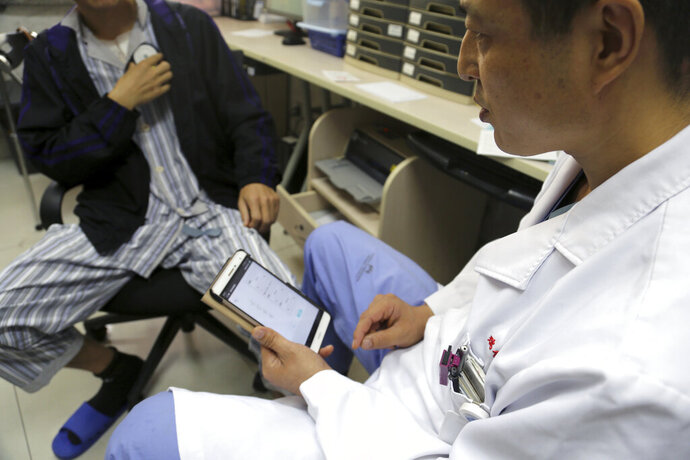 Dr. Li Dianyou uses a tablet computer to adjust the settings of a deep brain stimulation device implanted in the brain of a methamphetamine user named Yan, left, on Monday, Oct. 29, 2018, at Ruijin Hospital in Shanghai, China. Western attempts to push forward with human trials of DBS for drug addiction have foundered, even as China has emerged as a hub for this kind of research. But the vast suffering wrought by the U.S. opioid epidemic may be changing the risk-reward calculus. Now, the experimental surgery Yan underwent is coming to America. (AP Photo/Erika Kinetz)