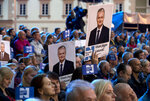 People hold posters with the image of Presidential candidate Gitanas Nauseda during debates between two candidates, Economist Gitanas Nauseda and Former finance minister Ingrida Simonyte, at the S. Daukanto Square, in front of the Presidential Palace in Vilnius, Lithuania, Friday, May 24, 2019. Gitanas Nauseda and a former finance minister Ingrida Simonyte held the top two spots in returns from Lithuania's presidential election Sunday, May 26 and appeared headed to a runoff ballot later this month to choose a successor to incumbent Dalia Grybauskaite. (AP Photo/Mindaugas Kulbis)