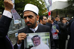 A member of the Turkish-Arab journalist association hold  a poster with the photo of missing Saudi writer Jamal Khashoggi, during a protest near the Saudi Arabia consulate in Istanbul, Monday, Oct. 8, 2018. Khashoggi, 59, went missing on Oct 2 while on a visit to the consulate in Istanbul for paperwork to marry his Turkish fiancée. The consulate insists the writer left its premises, contradicting Turkish officials. He had been living since last year in the U.S. in a self-imposed exile, in part due to the rise of Prince Mohammed, the son of King Salman. (AP Photo/Lefteris Pitarakis)