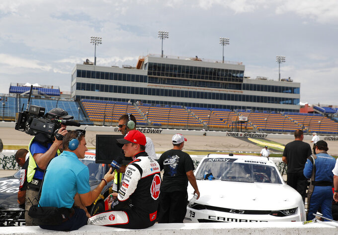 Christopher Bell, center, is interviewed after winning the pole during qualifying for the NASCAR Xfinity Series auto race, Saturday, July 27, 2019, at Iowa Speedway in Newton, Iowa. (AP Photo/Matthew Putney)