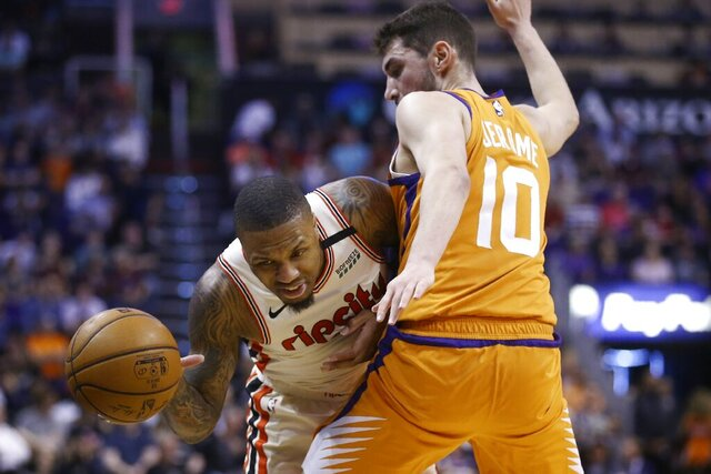 Portland Trail Blazers guard Damian Lillard, left, is fouled as he tries to dribble past Phoenix Suns guard Ty Jerome (10) during the first half of an NBA basketball game Friday, March 6, 2020, in Phoenix. (AP Photo/Ross D. Franklin)