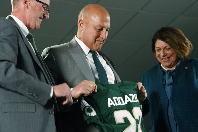 Steve Addazio, center, looks down at a jersey presented to him by athletic director Joe Parker, left, and President Joyce McConnell during an announcement that Addazio has been hired as the new head football coach at Colorado State University at a news conference at the school Thursday, Dec. 12, 2019, in Fort Collins, Colo. (AP Photo/David Zalubowski)