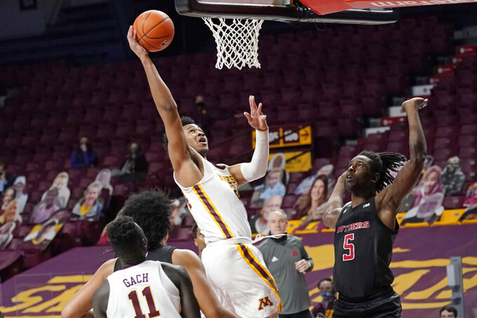 Minnesota's Eric Curry, left, lays up a shot as Rutgers' Cliff Omoruyi (5) watches in the first half of an NCAA college basketball game, Saturday, March 6, 2021, in Minneapolis. (AP Photo/Jim Mone)