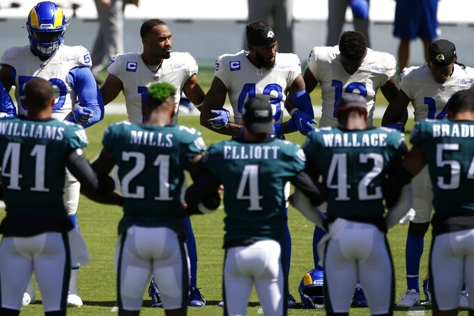 Los Angeles Rams and Philadelphia Eagles players lock arms before an NFL football game, Sunday, Sept. 20, 2020, in Philadelphia. (AP Photo/Laurence Kesterson)