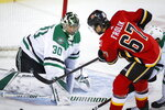 Dallas Stars goalie Ben Bishop, left, blocks a shot from Calgary Flames' Michael Frolik during the first period of an NHL hockey game Wednesday, Nov. 13, 2019, in Calgary, Alberta. (Jeff McIntosh/The Canadian Press via AP)