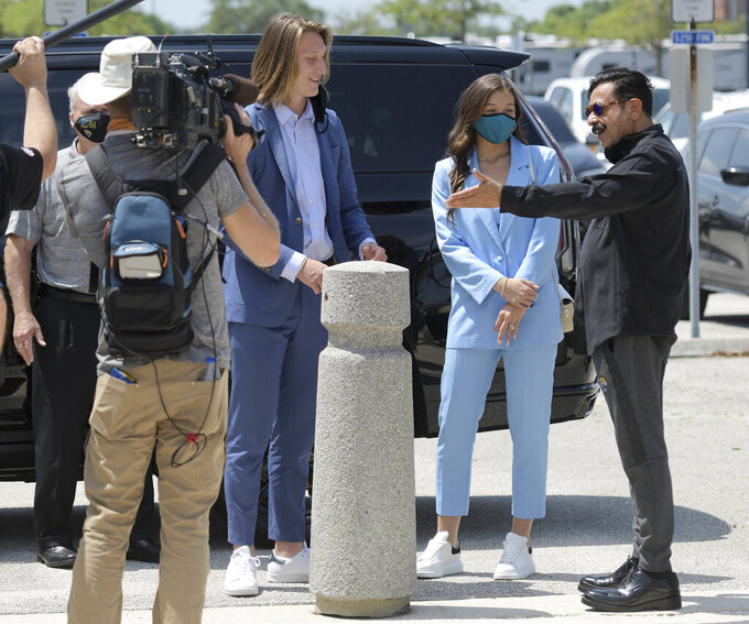 Jaguars owner Shad Khan, right, greets top draft pick Trevor Lawrence and his wife Marissa, center, as they arrived at TIAA Bank Field Friday, April 30, 2021, in Jacksonville, Fla.  (Bob Self/The Florida Times-Union via AP)
