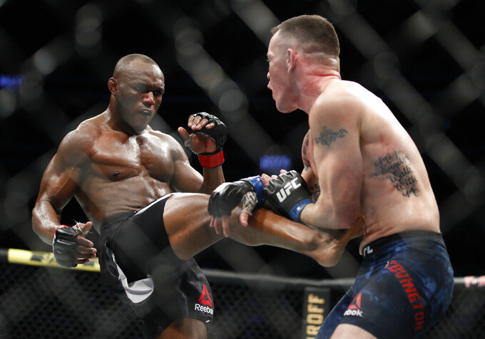 """FILE - Kamaru Usman kicks Colby Covington in a mixed martial arts welterweight championship bout at UFC 245 in Las Vegas, in this Saturday, Dec. 14, 2019, file photo. UFC 261 is being touted as the first full-capacity sporting event held indoors in more than a year. The card features three title fights, highlighted by a rematch between reigning welterweight champion Kamaru """"Nigerian Nightmare"""" Usman (18-1) and Jorge """"King of Miami"""" Masvidal (35-14). (AP Photo/John Locher, File)"""