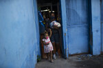 A woman and a child leave after receiving food donated by the Bees of Love Institute during the COVID-19 pandemic in the Rocinha slum of Rio de Janeiro, Brazil, Thursday, April 1, 2021. (AP Silvia Izquierdo)