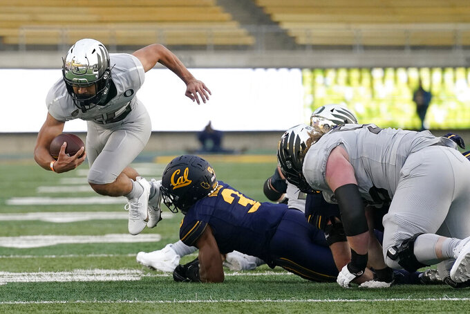 Oregon running back Travis Dye, left, runs against California safety Elijah Hicks (3) during the first half of an NCAA college football game in Berkeley, Calif., Saturday, Dec. 5, 2020. (AP Photo/Jeff Chiu)