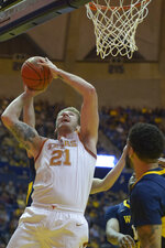 Texas forward Dylan Osetkowski (21) shoots during the first half of an NCAA college basketball game against West Virginia in Morgantown, W.Va., Saturday, Feb. 9, 2019. (AP Photo/Craig Hudson)