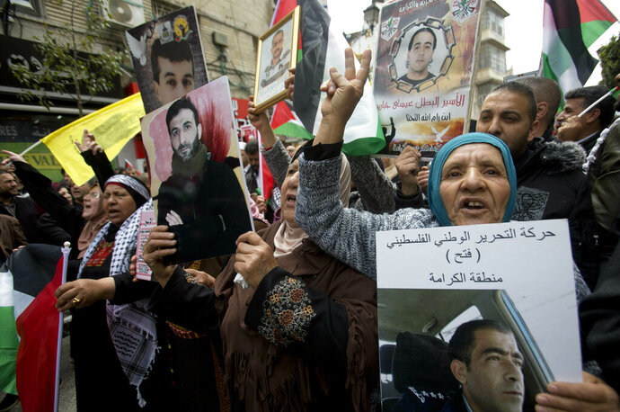 Relatives of Palestinians held in Israeli jails hold their portraits during a protest to mark