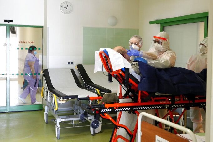 FILE - In this Friday, Feb. 12, 2021, file photo, medical workers move a covid-19 patient at a hospital overrun by the covid pandemic in Cheb, Czech Republic. The Czech government has decided to further tighten restrictive measures amid a surge of a highly contagious coronavirus variant in one of the hardest-hit European Union's nations. At the same time, the worsening situation has forced the Cabinet to abandon for now its plans to reopen all stores as soon as next week. (AP Photo/Petr David Josek/File)