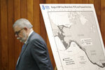 Federal Administrative Law Judge George Jordan steps past a display before a hearing to help determine whether a small American Indian tribe can once again hunt whales, Thursday, Nov. 14, 2019, in Seattle. The Makah Tribe, from the northwest corner of Washington state, conducted its last legal hunt in 1999, when its crew harpooned a gray whale from a cedar canoe. (AP Photo/Elaine Thompson)