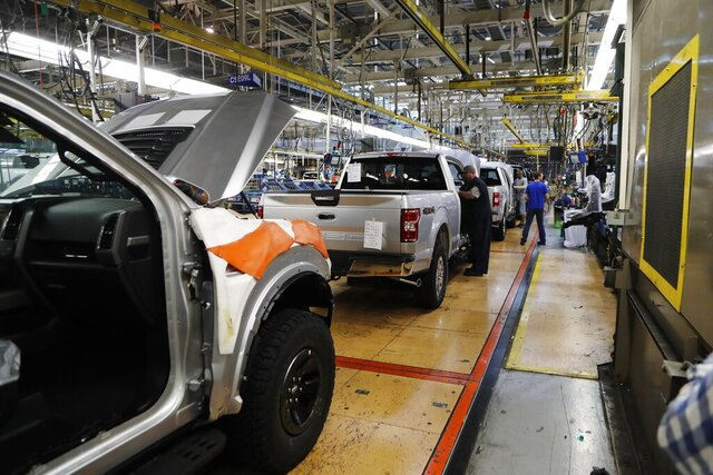 FILE - In this Sept. 27, 2018, file photo a United Auto Workers assemblyman works on a 2018 Ford F-150 truck being assembled at the Ford Rouge assembly plant in Dearborn, Mich. Ford is recalling its popular F-150 pickup truck in Canada to fix a problem with electric tailgate latches, but identical trucks aren't being recalled in the U.S. (AP Photo/Carlos Osorio, File)