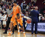Tennessee guard Jordan Bone (0) dribbles the ball in place to wind down the final seconds of an NCAA college basketball game in front of forward Grant Williams (2) as Tennessee head coach Rick Barnes and Texas A&M head coach Billy Kennedy shake hands in the background Saturday, Feb. 2, 2019, in College Station, Texas. (AP Photo/Michael Wyke)