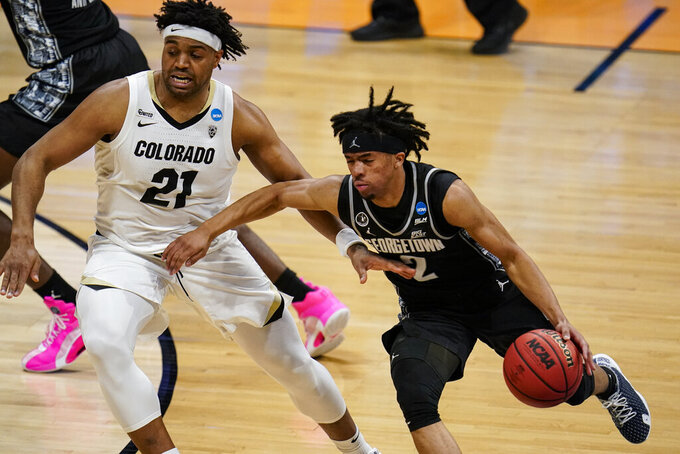 Georgetown guard Dante Harris (2) drives on Colorado forward Evan Battey (21) in the first half of a first-round game in the NCAA men's college basketball tournament at Hinkle Fieldhouse in Indianapolis, Saturday, March 20, 2021. (AP Photo/Michael Conroy)