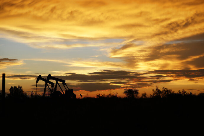 FILE- In this June 5, 2017, file photo pumpjacks work in an oil field at sunset after a thunderstorm passed through the area in Karnes City, Texas. The United States may have reclaimed the title of the world's biggest oil producer sooner than expected. The U.S. Energy Information Administration said Wednesday that America
