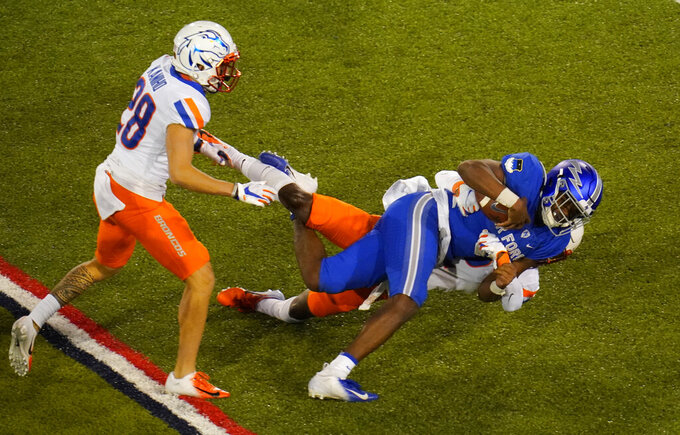 Air Force quarterback Warren Bryan, front right, is dragged down after a short gain by Boise State cornerback Jalen Walker as Boise State nose guard Kekaula Kaniho trails the play in the second half of an NCAA college football game Saturday, Oct. 31, 2020, at Air Force Academy, Colo. (AP Photo/David Zalubowski)