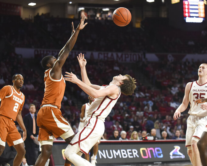Texas guard Andrew Jones (1) stops Oklahoma guard Austin Reaves (12) as he drives the basket during the first half of an NCAA college basketball game in Norman, Okla., Tuesday, March 3, 2020. (Kyle Phillips/The Norman Transcript via AP)
