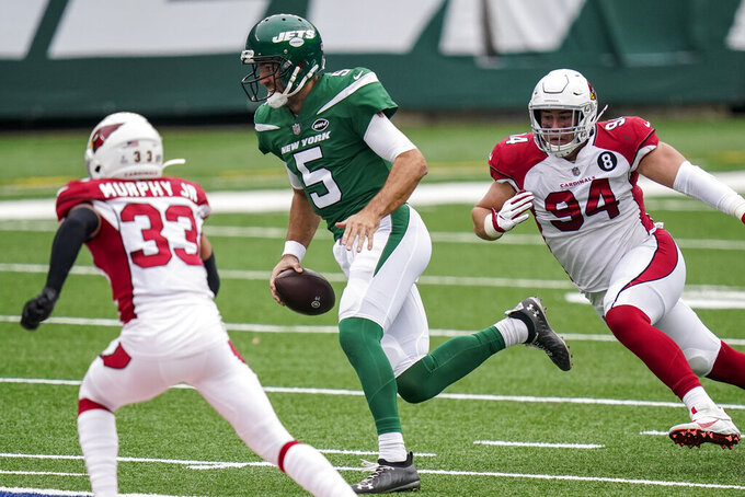 New York Jets quarterback Joe Flacco (5) runs the ball under pressure from Arizona Cardinals defensive end Zach Allen (94) during the first half of an NFL football game, Sunday, Oct. 11, 2020, in East Rutherford. (AP Photo/Frank Franklin II)
