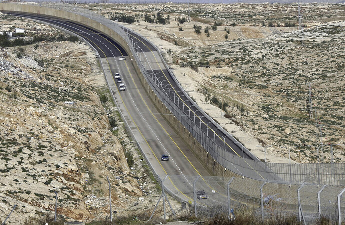 "FILE - This Jan. 10, 2019 file photo, shows a newly opened segregated West Bank highway near Jerusalem. Israel's government went on a spending binge in its West Bank settlements following the election of President Donald Trump, according to official data obtained by The Associated Press. Both supporters and detractors of the settlement movement have previously referred to a ""Trump effect,"" claiming the president's more lenient approach to the settlements would result in additional West Bank construction. (AP Photo/Mahmoud Illean, File)"