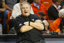 FILE- In this Jan. 6, 2020, file photo, West Virginia head coach Bob Huggins reacts during an NCAA college basketball game against Oklahoma State in Stillwater, Okla. College coaches endured a tense time waiting for for the NCAA to green light the 2020 basketball season. They knew there was a window the NCAA was looking at to start the season, likely sometime in late November or early December. They just didn't have an exact date. So they did the best they could to prepare for the big moment, yet still found themselves in a scramble once it actually happened. (AP Photo/Sue Ogrocki, File)