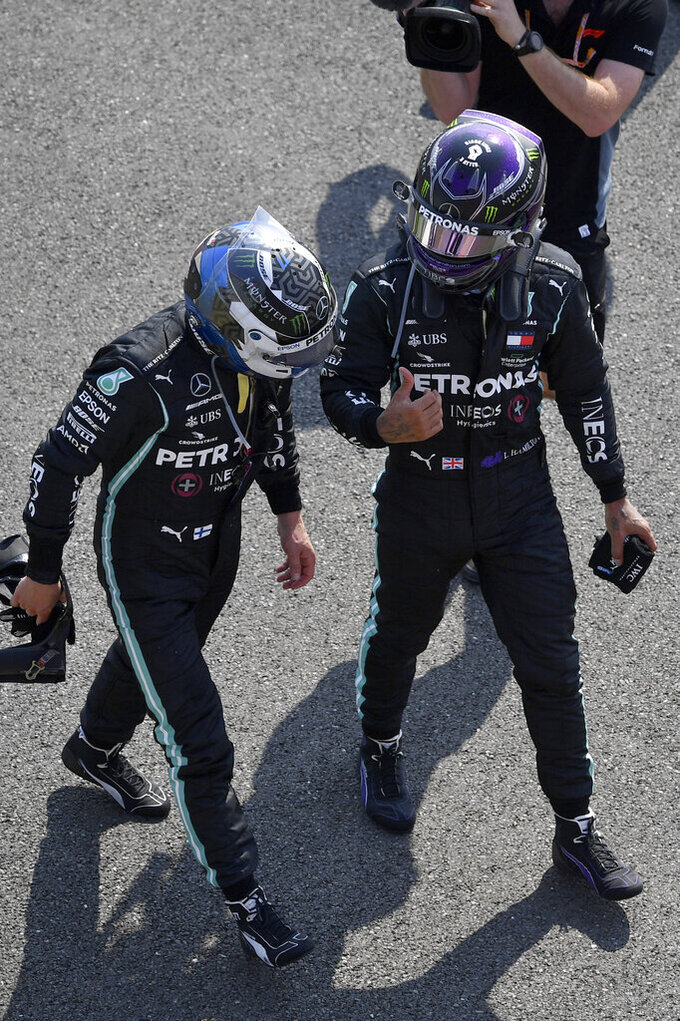 Second placed Mercedes driver Lewis Hamilton of Britain talks with teammate and third placed Valtteri Bottas of Finland, left, after finishing the 70th Anniversary Formula One Grand Prix at the Silverstone circuit, Silverstone, England, Sunday, Aug. 9, 2020. (Ben Stansall, Pool Photo via AP)