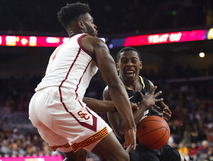 Colorado guard McKinley Wright IV, right, loses the handle on the ball as Southern California guard Daniel Utomi defends during the second half of an NCAA college basketball game Saturday, Feb. 1, 2020 in Los Angeles. (AP Photo/Kyusung Gong)