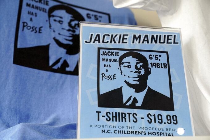 """ee-shirts showing former North Carolina basketball player Jackie Manuel's likeness are seen for sale at Underground Printing in Chapel Hill, N.C., Thursday, July 15, 2021. The Ann Arbor-based company Underground Printing is positioned to help athletes and its business make money with merchandise it can sell online. """"It's the same service that students and groups and departments use anyway so this is just an avenue for athletes to do the same thing,"""" said owner Rishi Narayan, whose company has 25 stores from Chapel Hill to Norman, Oklahoma. (AP Photo/Gerry Broome)"""