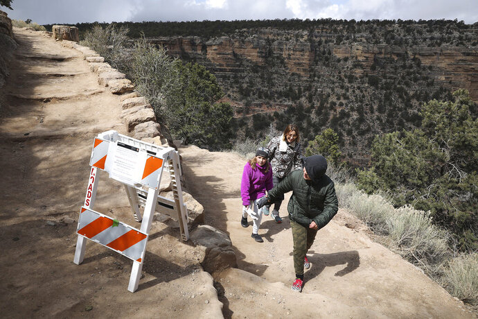 In this March 27, 2020 photo, Shelly Clayton, center, walks up the Bright Angel Trail at Grand Canyon National Park, Ariz., with her children Audrey Kuhar, 11, left, and Cooper Kuhar, 11. The park has closed restaurants, lodges, visitor centers, campgrounds and other services as it awaits approval from the federal government for a full shutdown. (Jake Bacon/Arizona Daily Sun via AP)