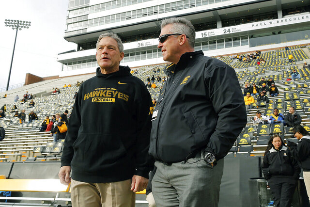 FILE - In this Oct. 26, 2013, file photo, Iowa head coach Kirk Ferentz talks with Iowa Athletics Director Gary Barta before an NCAA college football game against Northwestern at Kinnick Stadium in Iowa City, Iowa. The Iowa football program's culture has suffered from racial bias against Black players and bullying by a small number of current and former coaches, according to an investigation report released Thursday, July 30, 2020 (AP Photo/Brian Ray, File)