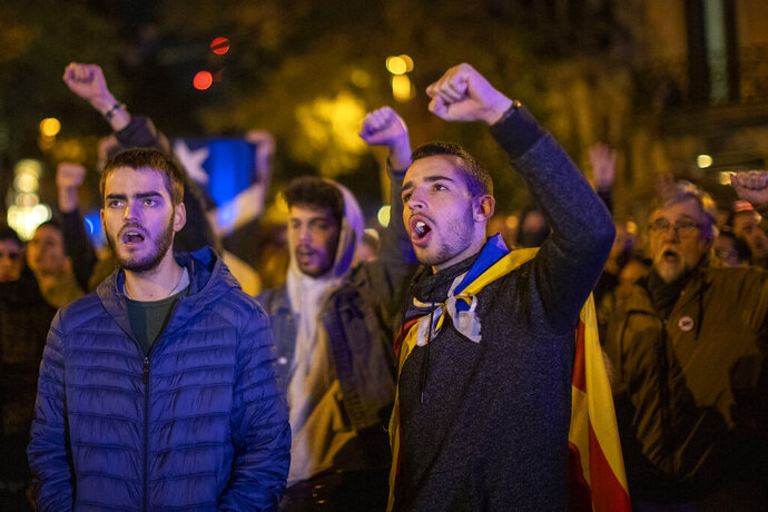 Catalan pro-independence demonstrators shout slogans in front of the Spanish regional Government Office, during a demonstration in Barcelona, Spain, Monday, Nov.11, 2019. Barcelona and the rest of the restive Spanish region of Catalonia are reeling from several days of protests for the sentencing of 12 separatist leaders to lengthy prison sentences. (AP Photo/Emilio Morenatti)