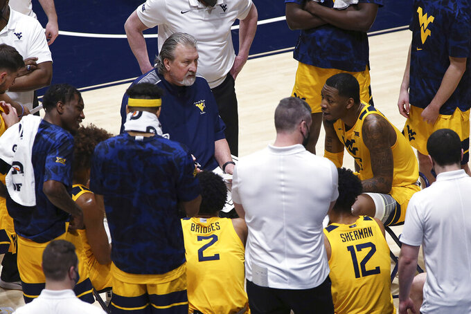 West Virginia coach Bob Huggins speaks with players during the second half of the team's NCAA college basketball game against Baylor on Tuesday, March 2, 2021, in Morgantown, W.Va. (AP Photo/Kathleen Batten)