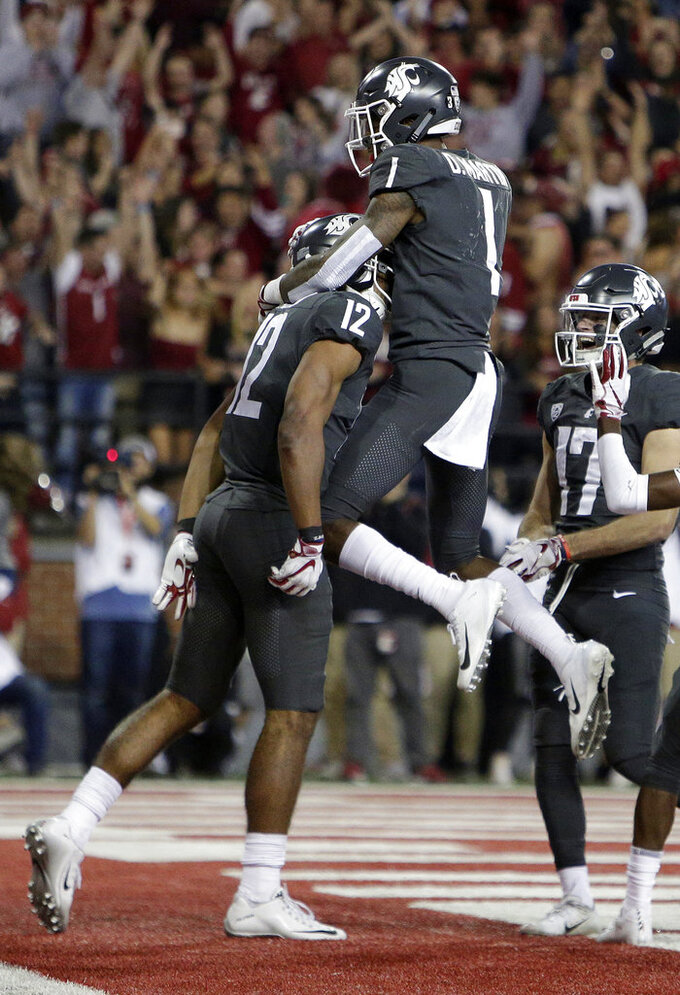 Washington State wide receiver Dezmon Patmon (12) celebrates his touchdown catch with teammate wide receiver Davontavean Martin (1) during the second half of an NCAA college football game against Oregon in Pullman, Wash., Saturday, Oct. 20, 2018. Washington State won 34-20. (AP Photo/Young Kwak)