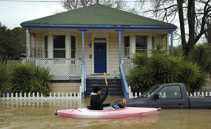 A woman with a dog sails a kayak on a flooded street in Guerneville, north of San Francisco on Wednesday, Feb. 27, 2019. (Kent Porter/The Press Democrat via AP)