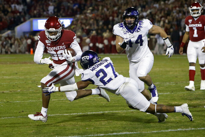Oklahoma running back Kennedy Brooks (26) carries past TCU safety Ar'Darius Washington (27) and defensive end Colt Ellison in the first half of an NCAA college football game in Norman, Okla., Saturday, Nov. 23, 2019. (AP Photo/Sue Ogrocki)