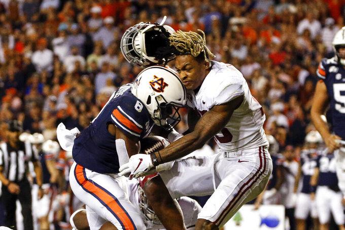 Alabama defensive back Xavier McKinney (15) loses his helmet as Auburn running back Shaun Shivers (8) runs through him for a touchdown during the second half of an NCAA college football game Saturday, Nov. 30, 2019, in Auburn, Ala. (AP Photo/Butch Dill)