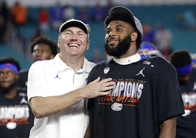 Florida head coach Dan Mullen, left, stands with running back Lamical Perine (2) after the Orange Bowl NCAA college football game against Virginia, Monday, Dec. 30, 2019, in Miami Gardens, Fla. Florida won 36-28. Perine was the MVP. (AP Photo/Lynne Sladky)