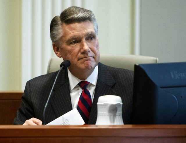 FILE - In this Feb. 21, 2019, file photo, Mark Harris, Republican candidate in North Carolina's 9th congressional race, makes a statement before the state board of elections calling for a new election during the fourth day of a public evidentiary hearing on the 9th congressional district voting irregularities investigation at the North Carolina State Bar in Raleigh, N.C.  A local prosecutor says the former North Carolina congressional candidate won't face state charges in an absentee ballot fraud investigation that's already led to indictments against his hired political operative and a new election.(Travis Long/The News & Observer via AP, Pool, File)