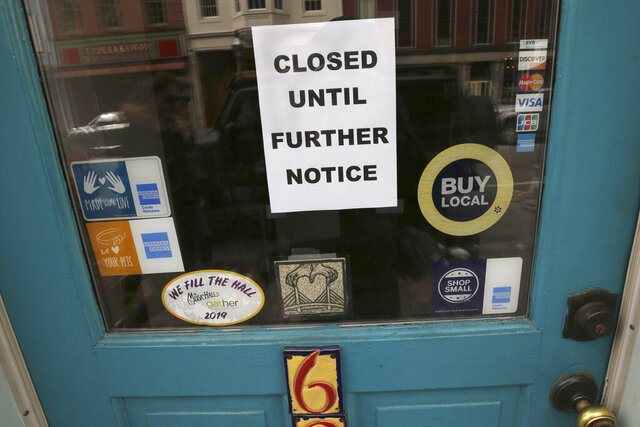 FILE - In this March 25, 2020 file photo,  a closed sign hangs in the window of a shop in Portsmouth, N.H., due to caronavirus concerns.  The Federal Reserve is taking additional steps to provide up to $2.3 trillion in loans to suport American households and businesses as well as local governments as they deal with the coronavirus. The Fed said Thursday, April 9,  among the actions it is taking is the activation of a Main Street Lending Program that was authorized by the $2.3 trillion economic relief bill pass by Congress last month. (AP Photo/Charles Krupa, File)