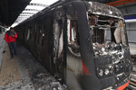 Subway cars burnt by protesters are parked at the Elisa Correa station in Santiago, Chile, Sunday, Oct. 20, 2019. Chilean President Sebastián Piñera on Saturday announced the suspension of a subway fare hike that had prompted violent student protests, less than a day after he declared a state of emergency amid rioting and commuter chaos in the capital. (AP Photo/Esteban Felix)