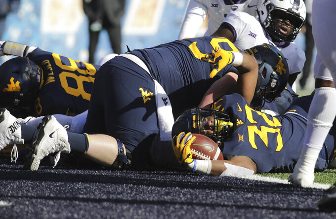 West Virginia running back Martell Pettaway (32) crosses the goal line for a touchdown during the first half of an NCAA college football game against TCU, Saturday, Nov. 10, 2018, in Morgantown, W.Va. (AP Photo/Raymond Thompson)