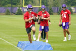 Minnesota Vikings quarterbacks Nate Stanley, right, and Jake Browning, center, watch Kirk Cousins hop-step through a drill during the NFL football team's training camp, Thursday, Aug. 5, 2021, in Eagan, Minn. (AP Photo/Jim Mone)